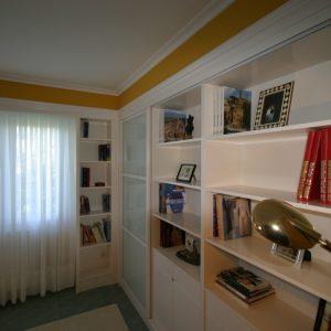 Librería lacada en blanco con puertas correderas y cristal lacobel
